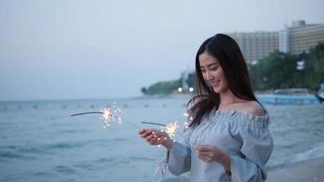 menina asiática segurando brilhos de luz à beira-mar.