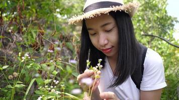 mujer asiática huele las flores en el bosque.