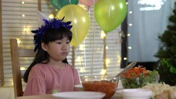Chinese little girl unhappy by the dinner table at home.
