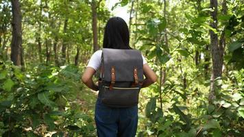 Hermosa joven asiática camina a través de una selva con una mochila