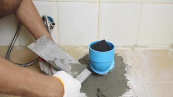 usando ferramentas de gesso ao redor do tubo de pvc para drenar os resíduos.