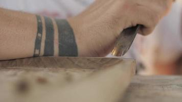 artesão fazendo uma bandeja de chá com escultura em madeira