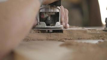 carpinteiro trabalha com fresa manual elétrica