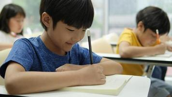 Asian student learning and writing in the classroom at school.