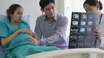 Asian Man and Pregnant Woman Getting Serious News from Doctor.