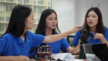 Asian engineers design robot circuit and arm.