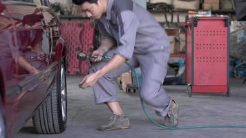 Hombre técnico comprobando la presión de los neumáticos en un garaje.