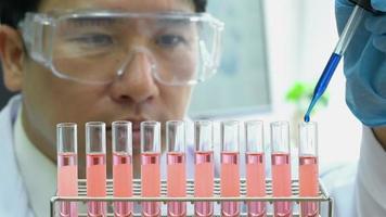 asiatischer Mann experimentiert mit Chemikalien im Wissenschaftslabor. video
