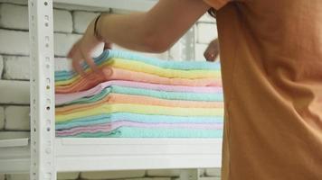 mulher fazendo tarefas colocando toalhas na prateleira