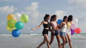 groupe de filles sur la plage et tenant des ballons