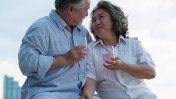 Asian senior couple drinking beverages and relaxing on the beach