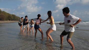 grupo adolescente asiático jogando cabo de guerra na praia