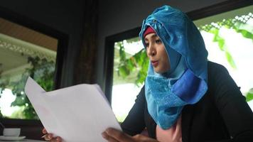 Woman wearing hijab excited with results in business papers. video