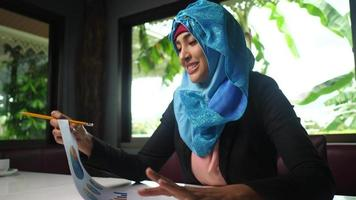 Young Arabic woman working at home with business chart video