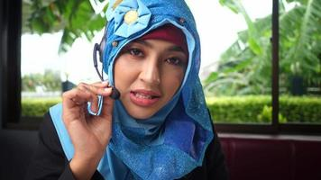 Young Arab woman working in a call center using a headset video