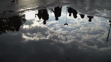 pessoas caminhando e reflexos de nuvens em uma poça