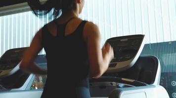 mujer atlética corriendo en caminadora.
