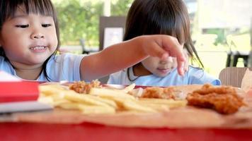 crianças comendo comida frita em uma loja de fast food