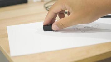 la main efface les marques de crayon
