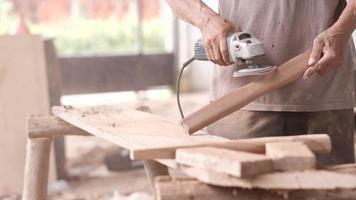 artesão usando uma máquina de polir em um pedaço de madeira