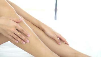 Frau, die Feuchtigkeitscreme auf ihren Beinen ausbreitet