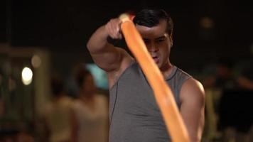 homem atlético balançando cordas na academia