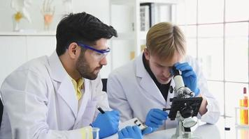 equipe de cientistas usando um microscópio e escrevendo um relatório