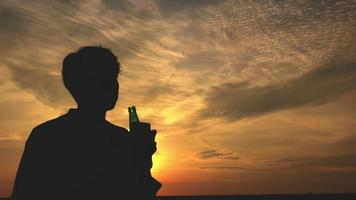 Silhouette of A Man Drinking from A Bottle
