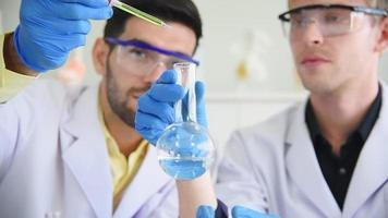Wissenschaftler pipettieren eine bunte flüssige Probe in einen Glaskolben