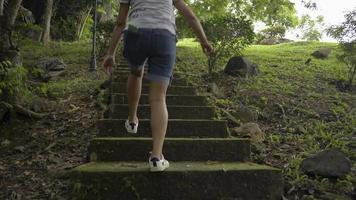 vista traseira da mulher subindo na velha escada de concreto