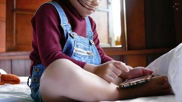 Young girl playing on a smartphone.
