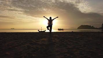 mulher pratica ioga na praia video