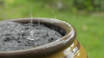 Close up the rain falling into a clay jar.