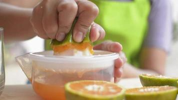 Hands squeezing orange pouring juice into a glass video