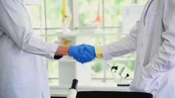 pessoas em jalecos apertando a mão em um laboratório