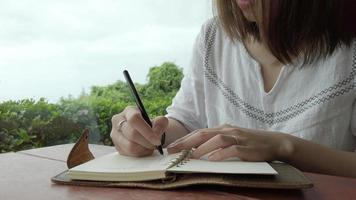 uma mulher escrevendo em um caderno