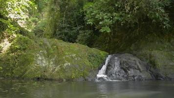 pequena cachoeira fluindo pelas montanhas. video