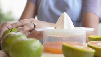 feche as mãos apertando laranjas em um espremedor manual.