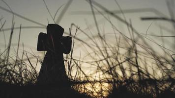 silhueta de uma cruz de pedra em um campo