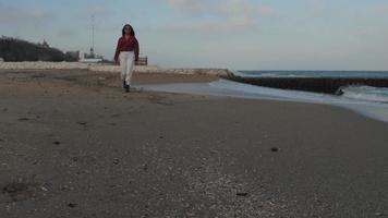 menina caminha na praia