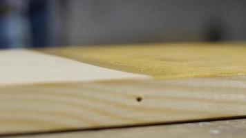 mão aplica impregnação de madeira a uma placa com uma esponja