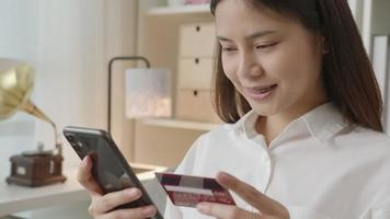 mulher digitando em seu smartphone e segurando um cartão de crédito