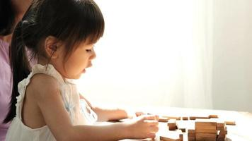 Little Asian girl plays with blocks