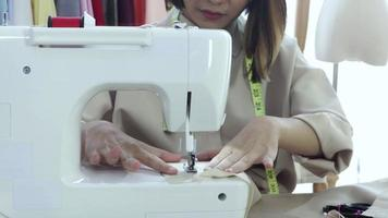 Asian woman is sitting sewing and designing her tailoring. video