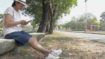 mujer asiática sentada bajo el árbol y usando un teléfono móvil