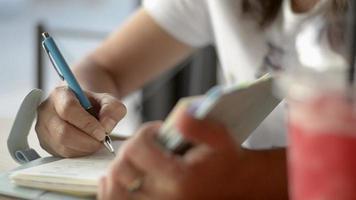 mulher asiática sentado e escrevendo no diário na loja de bebidas.