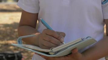 mulher caminhando e escrevendo no diário em um parque público