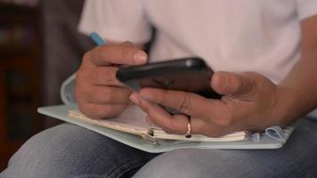 Person sitting, using cellphone, and writing on diary