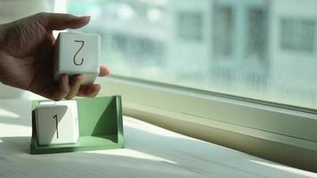 Mano cambiando un bloque de calendario de madera blanca del 18 al 19