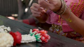 Hands of A Traditionally Dressed Woman Weaving a Jasmine Garland